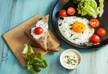 Завтрак из яичницы с овощами, томатами и салатом на столе.