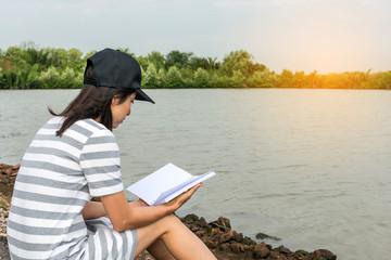 young asian woman sit near lake
