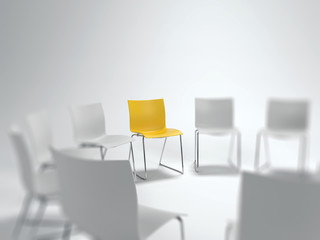 Individual yellow chair in a circle of white ones