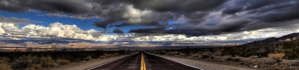 Pnorama of a lonely road through Mojave Desert under a dramatic sky.