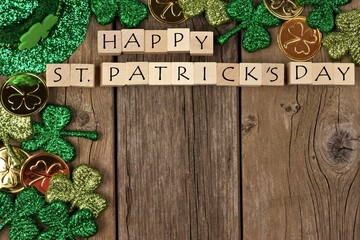 Happy St Patricks Day wooden blocks with shamrocks decor on a rustic wood background