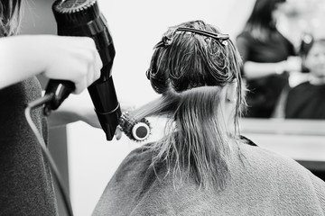 Hairdresser dry and brush woman hair