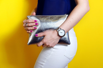 Wall Mural - Fashion woman close up silver clutch bag and watch accessory