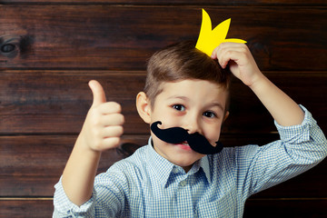 A kid with props for a photo booth gives a thumbs-up.. The child