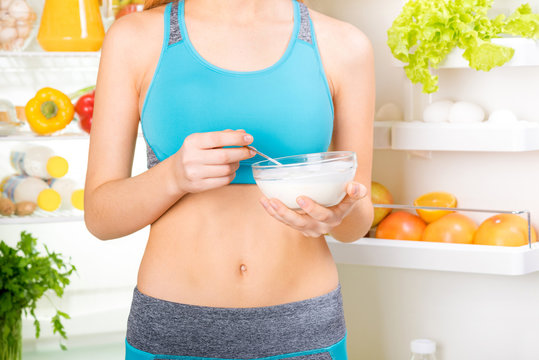 Young woman eating a yogurt and staying near the fridge full of health food. Fitness and healthy lifestyle concept.