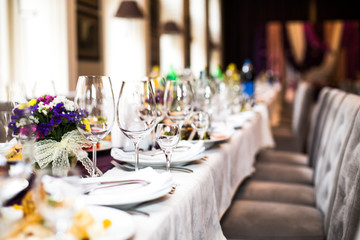 Sparkling glassware stands on long table prepared for wedding di