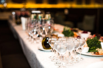 Wineglasses with water stand on rich served dinner table