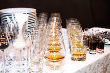 Glasses with different kinds of alcohol stand served in rows on