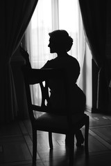Silhouette of a woman sitting on soft chair and watching herself