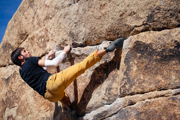 Young caucasian man climbs a granite cliff in the desert