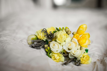 Yellow boutonniere lies on white blanket