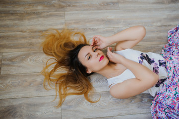 happy young woman lying on wooden