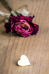 dried rose and chocolate heart on a wooden table, copy space