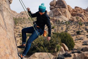 Young african american woman climbs along a granite cliff in the desert dressed for cold weather