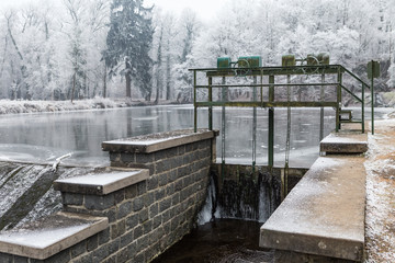 Hand operated wheel controls and Sluice gate on pond