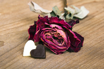dried rose two chocolate hearts on a wooden table, copy space