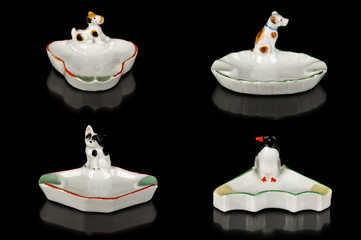 Collection of four white vintage porcelain ash trays with an animal motif on a black background