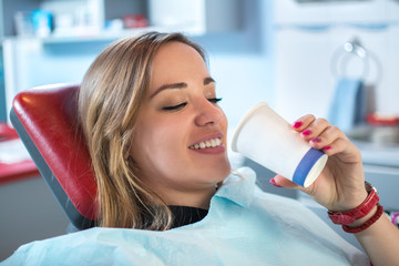 Smiling woman is taking a glass of water in dental office.
