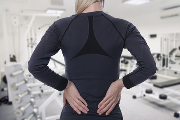 Athletic fitness woman suffering from lower back pain in gym. Sports exercising injury.
