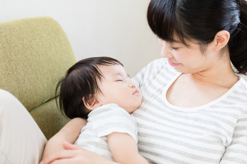 asian mother and baby relaxing on the sofa