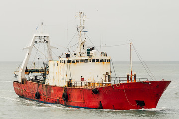 Red fishing boat sailing alone on the ocean near Mar del Plata,