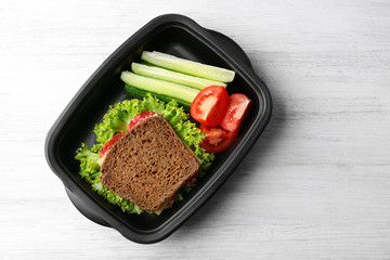 Lunch box with food on wooden background, top view
