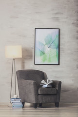 Armchair with books on gray wall background
