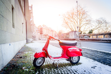 Red retro motorcycle scooter parked along a street covered with snow in the winter in the city of Bern, Switzerland.