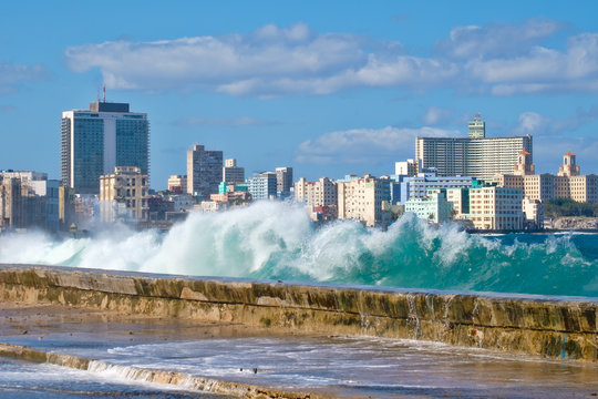 The Havana skyline with waves crashing on the Malecon seawall