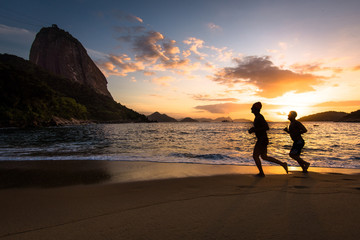 Silhouettes of Two Men Running in the Beach by Sunrise with the Sugarloaf Mountain in the Horizon