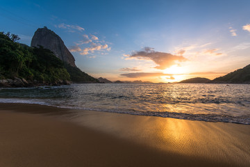 Wall Mural - Beautiful Sunrise in the Beach with Few Clouds in the Sky, Sugarloaf Mountain in the Horizon, and Reflection of Sun in the Sand, Rio de Janeiro, Brazil