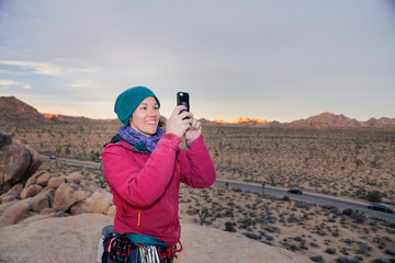 Young caucasian woman dressed for cold weather rock climbing in the desert takes a cell phone picture