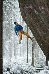 Outdoor winter sport. Rock climber ascending a challenging cliff. Extreme sport climbing.