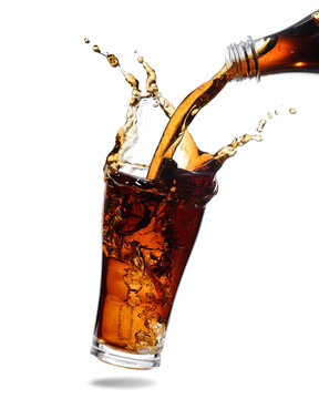 Pouring cola from bottle into glass with splashing., Isolated white background.