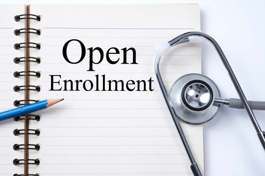 Stethoscope on notebook and pencil with Open Enrollment words as