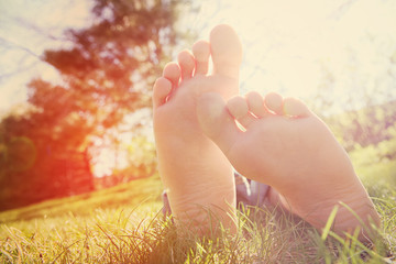Barefoot person lying on green grass outdoors.  Instagram effect