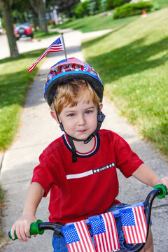 Boy riding his bicycle in a 4th of July neighborhood parade.