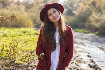 cute girl in red cardigan and hat in autumn