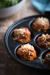 Italian meatballs in a divided cast iron pan. Selective focus, close up