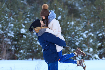 Young couple hugging and kissing in winter forest