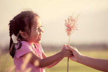 Happy asian little girl giving grass flower to her mother