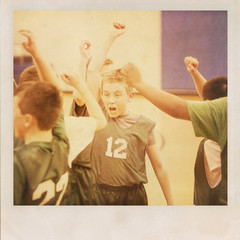 Young basketball player cheering with his team.  Vintage grunge