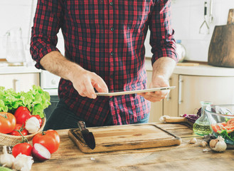 Man following recipe healthy food in kitchen at home