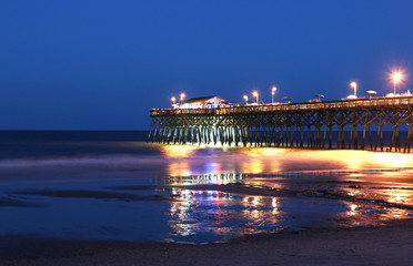Atlantic ocean pier with bright lightening during the beautiful summer night. Surfside Beach, Myrtle Beach area, South Carolina, USA. Horizontal composition, long exposure.