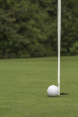Golf ball close to pin and hole