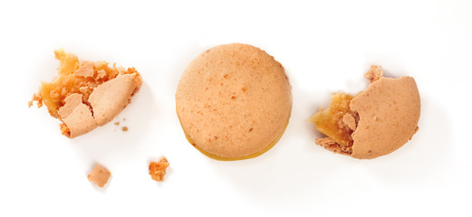 Macarons and crumbs on white background