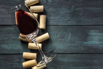 Glass of red wine and corks on dark background