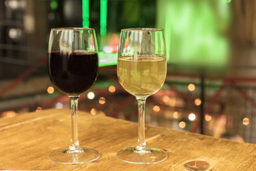Red and white wine glasses on blurred lights background