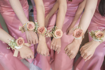 close up of hands bridesmaid with flower and pink dress