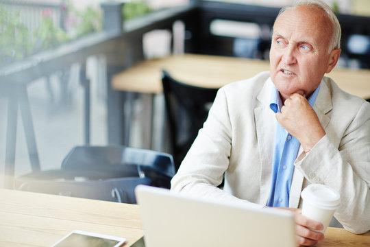 Concerned Mature Businessman in Cafe